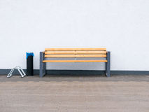 Empty modern outdoor bench. Empty modern outdoor bench and bike rack and industrial ashtray at wall background Stock Photos