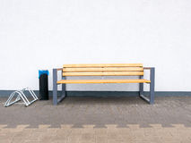 Empty modern outdoor bench. Empty modern outdoor bench and bike rack and industrial ashtray at wall background Stock Photo