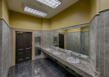 Empty modern restroom. An empty modern restroom with three sinks and ceramic tile Royalty Free Stock Photo