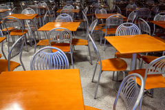 Empty modern style canteen with nobody using area. Silver shiny steel chairs and wooden tables in indoor industrial and modern style canteen - empty with nobody Royalty Free Stock Image