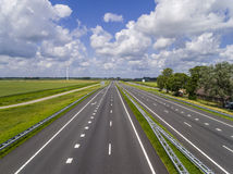 Empty motorway. Motorway with no traffic except far in the distance in a flat green landscape with a beautiful half cloud sky Stock Images