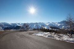 Empty mountain road on Alps with curve in a sunny day Stock Photo
