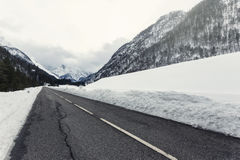 Empty mountain road on a cloudy winter day Royalty Free Stock Image