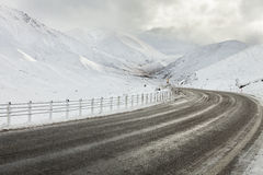 Empty mountain road on a cloudy winter day. Royalty Free Stock Photos