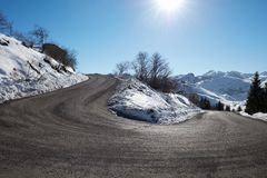 Empty mountain road curve on Alps with snow on sides, blue sky Royalty Free Stock Photography
