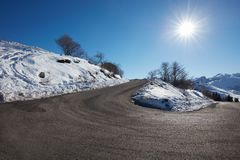 Empty mountain road curve on Alps with snow on sides, blue sky Stock Images