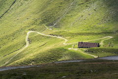 Empty mountain road meander to lonesome house in austrian Alps Stock Photos