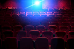 Empty movie theater with projection light. Falling into the lens Royalty Free Stock Photos
