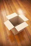 Empty Moving Box Background. An empty moving box on wood floorboards background with space for copy Stock Images