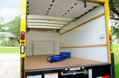 Empty moving truck with dolly in back. Empty yellow moving truck with blue dolly in back Stock Photography