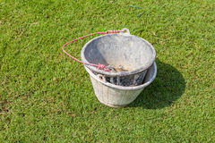 Empty muddy buckets and red holder leave on the green grass gard Stock Images