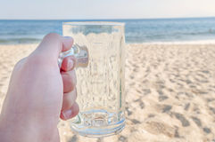 Empty mug of drained fresh beer on the beach Stock Photos