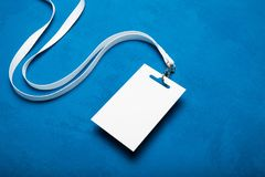 Empty name tag with white neckband on blue background stock photos