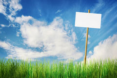 Empty nameplate on a stick at bright green field Stock Photo