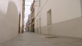 Empty narrow street in catalonian village with pigeons.