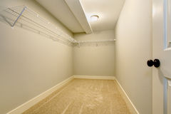 Empty narrow walk-in closet with shelves and carpet floor. Northwest, USA royalty free stock photography