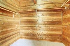 Empty narrow walk-in closet with wooden panel trim walls Stock Photos