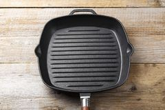 Empty net cast iron grill pan on wooden background. Space for text stock photography