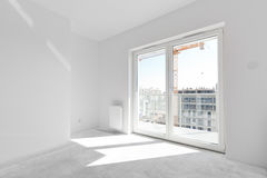 Empty new apartment for interior arrangement. Window light. Empty new apartment room for interior arrangement. Light from the window, white walls, concrete floor Royalty Free Stock Photo