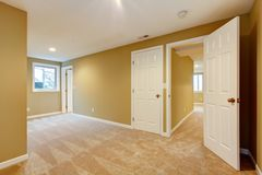 Empty new bedroom with many doors and beige carpet. Stock Image
