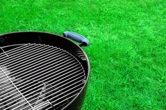 Empty New Clean BBQ Grill Close-up. Empty New Opened Clean BBQ Charcoal Kettle Grill Close-up On The Spring Grass Background Stock Photography