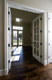 Empty new modern home doorway. Lovely interior doorway and hall of empty new modern home with dark hard wood floors offered for sale stock photos