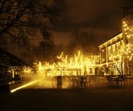 Empty night restaurant, lot of tables and chairs with noone, mag. Ic fairy lights on trees like christmas celebration close up Stock Images