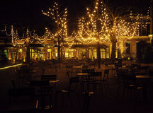 Empty night restaurant, lot of tables and chairs with noone, magic fairy lights on trees like christmas. Celebration Stock Photo