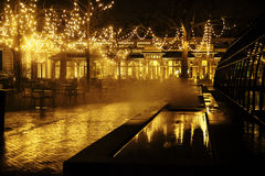 Empty night restaurant, lot of tables and chairs with noone, magic fairy lights on trees like christmas celebration. Close up Stock Photography
