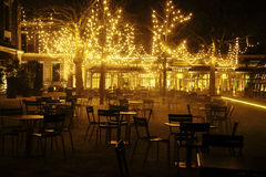 Empty night restaurant, lot of tables and chairs with noone, magic fairy lights on trees like christmas celebration. Close up Stock Image