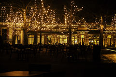 Empty night restaurant, lot of tables and chairs with noone, magic fairy lights on trees like christmas celebration. Close up Royalty Free Stock Image