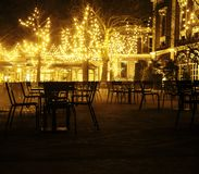 Empty night restaurant, lot of tables and chairs with noone, magic fairy lights on trees like christmas celebration. Close up Royalty Free Stock Photo