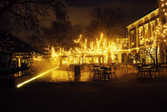 Empty night restaurant, lot of tables and chairs with noone, magic fairy lights on trees like christmas, luxury. Lifestyle concept Stock Photos