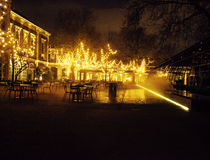 Empty night restaurant, lot of tables and chairs with noone, magic fairy lights on trees like christmas, luxury. Lifestyle concept, Amsterdam Stock Photos