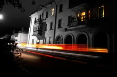 Empty night street of a European city with small houses, car lights in blur Royalty Free Stock Photos