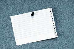 Empty note. Empty ripped note pinned on corkboard; blue tint Royalty Free Stock Image