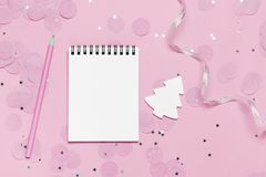 Empty note book - christmas and new year mock up template with pink confetti on pink background. And white wooden christmas tree. Bright and festive holiday royalty free stock photography