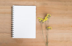 Empty note book and yellow flowers wooden background. View from Royalty Free Stock Photos