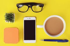 Empty note paper with plastic cup of coffee, pen, phone and glasses. Empty note paper with plastic cup of coffee, pen, notepad, phone and glasses. Yellow royalty free stock images