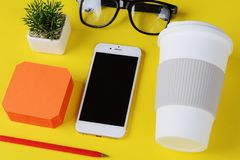 Empty note paper with plastic cup of coffee, pen, phone and glasses. Yellow background royalty free stock images