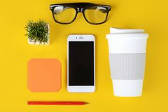 Empty note paper with plastic cup of coffee, pen, phone and glasses. Yellow background royalty free stock image