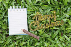 Empty note paper and wooden pencil on green lawn and have gold t Royalty Free Stock Photo