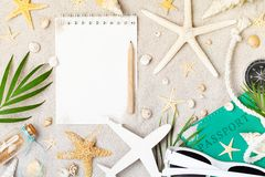 Empty notebook with accessories for planning summer holidays, travel and vacation on sand background top view. Flat lay style royalty free stock photo