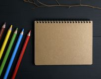 Notebook with brown pages and multicolored wooden pencils. Empty notebook with brown pages and multicolored wooden pencils on a black table, top view Stock Images