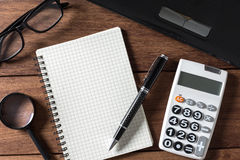 Empty notebook with calculator and laptop on desk office Stock Photography