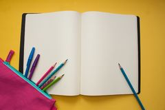 Empty notebook and colorful pencils on yellow background stock photography