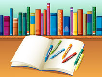 An empty notebook with crayons in front of the shelf with books Royalty Free Stock Image