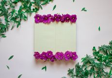 Empty notebook decorated purple flowers on a white background, top view. Notepad decorated with green leaves and violet. Flat lay. vector illustration
