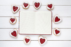 Empty notebook frame for design text and heart shaped cookies on white wooden background. Stock Image