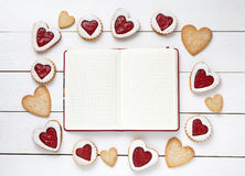 Empty notebook frame for design text and heart shaped cookies on white wooden background. Stock Photo
